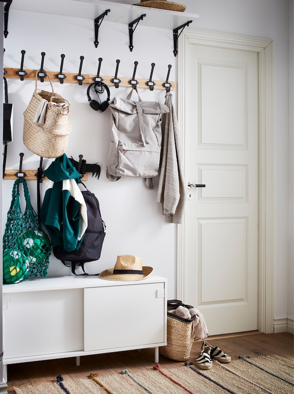A hallway with hooks holding jackets and bags, a broad shelf high up and a white MACKAPÄR bench with storage compartments.