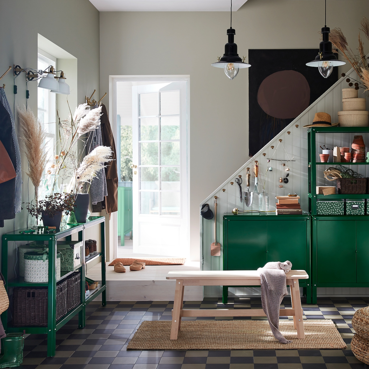A hallway with KOLBJÖRN shelving units and cabinets in green, a bench in birch, a jute rug and two black pendant lamps.