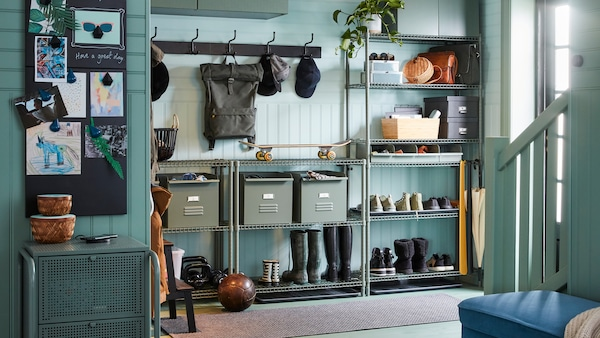 A hallway with OMAR shelving holding shoes, boots and metal REJSA boxes and two PINNIG racks with 3 hooks on the wall.