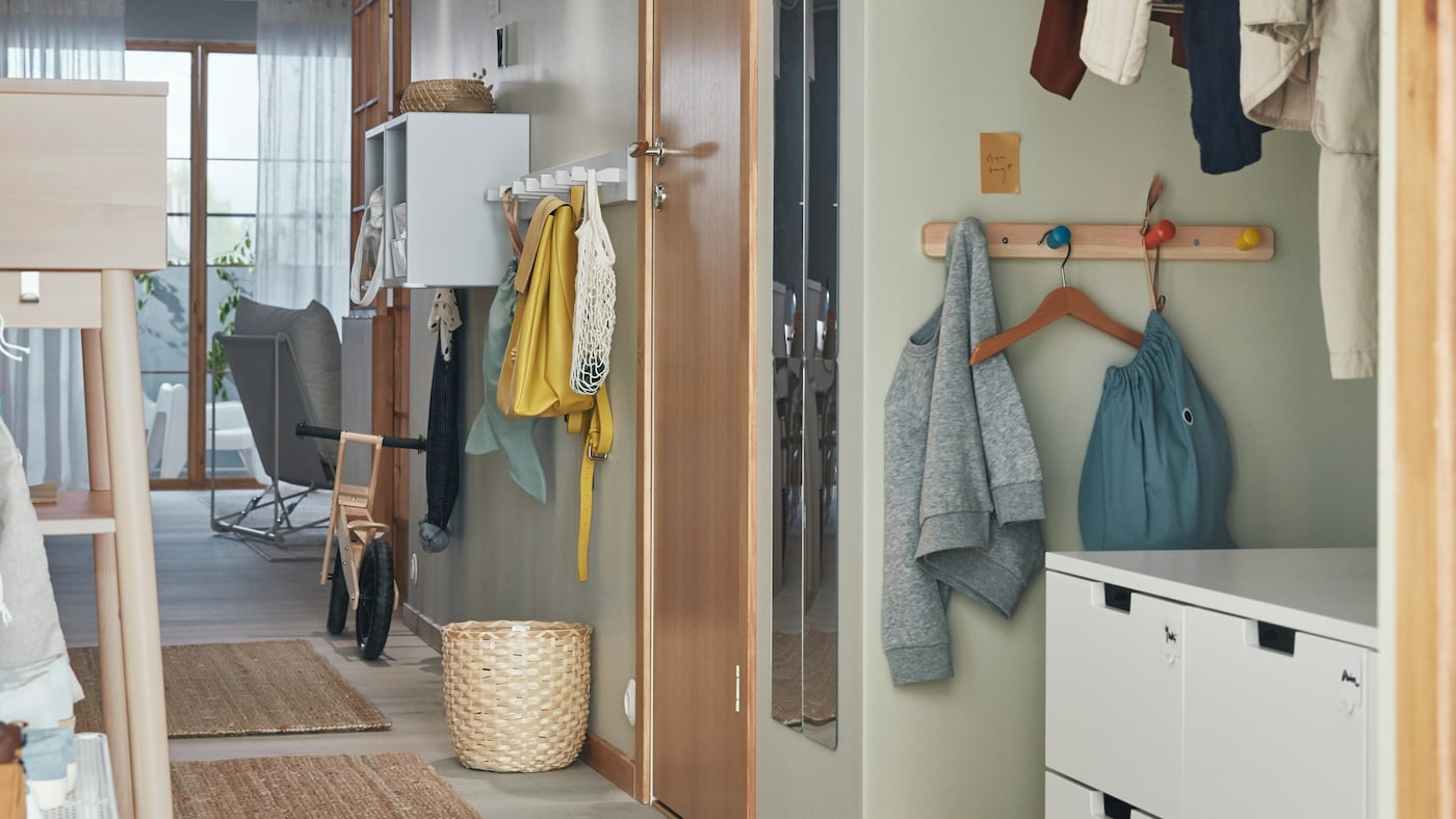 A hallway with rugs on the floor, a NORDLI chest of drawers, and FLISAT and KUBBIS hook racks and EKET shelving on the wall.