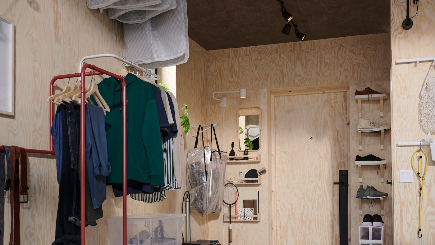 A hallway with shelving, hooks and a red NIKKEBY clothes rack and a white MULIG clothes bar both holding clothing.