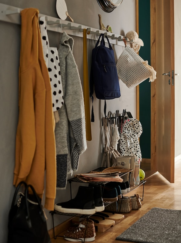A hallway with three black GREJIG shoe racks, coats and bags hanging on two white KUBBIS racks with seven hooks in a row.