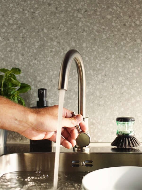 A hand controlling the flow of water from an arched mixer tap into a sink, in front of a grey wall panel with a plant beside it.