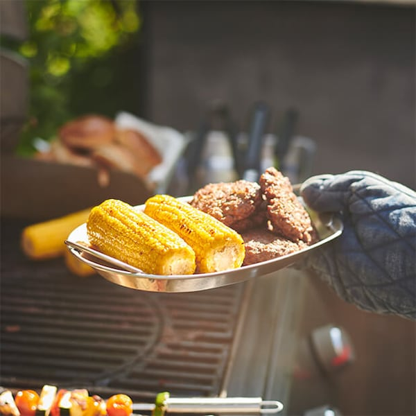 A hand covered by an oven mit holding a try of food over a barbecue grill