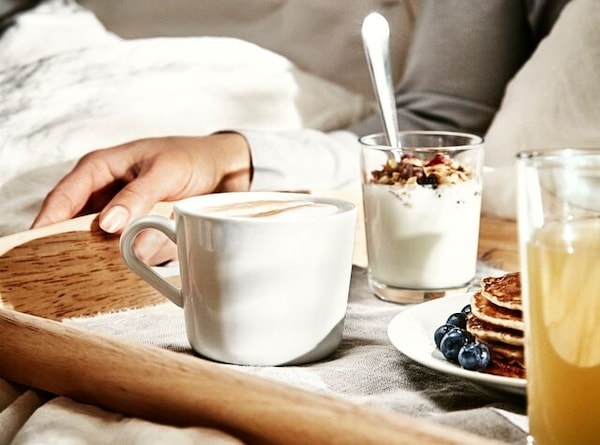 A hand holding a breakfast tray with pancakes, juice, a white mug of cappuccino and glass with yogurt shown in a bed.