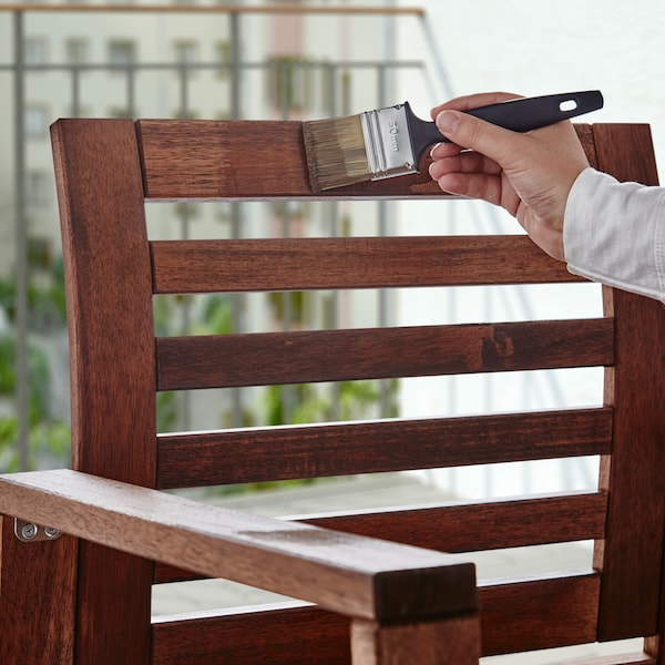 A hand holding a brush and applying VÅRDA wood stain to a wooden armchair.