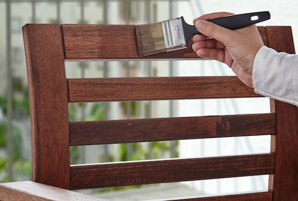 A hand holding a brush, covering the stained backrest of a wooden chair outdoors.