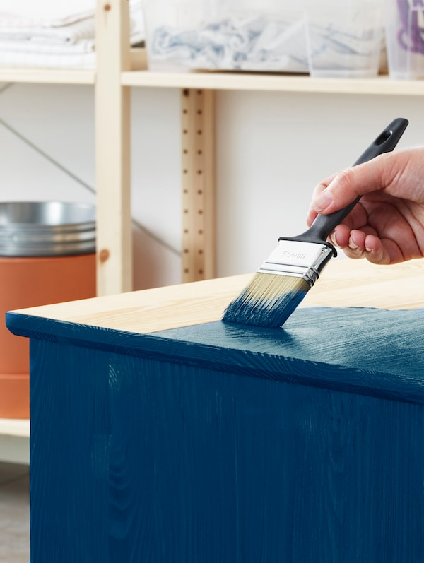 A hand holding a large paintbrush is painting a light brown wooden cupboard blue.