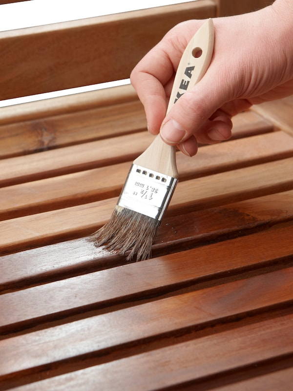 A hand holding a paintbrush, painting the wooden slats of stained outdoor furniture.