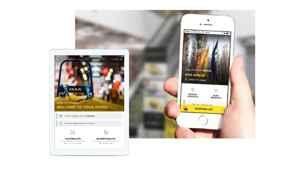 A hand holding a smart phone displaying the IKEA store app.