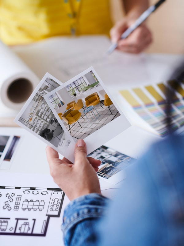 A hand holding photos of chairs and other items, while an IKEA co-worker in yellow top makes notes in the background.