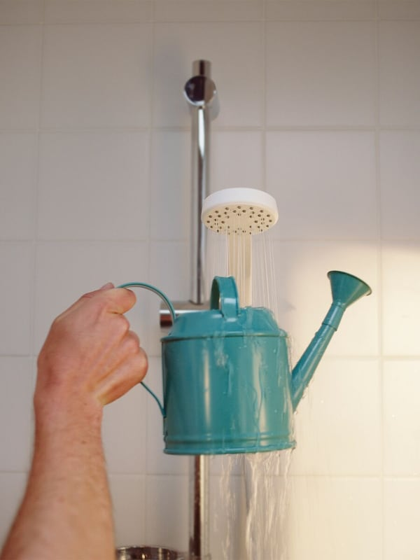 A hand holds a small blue watering can under a running shower.