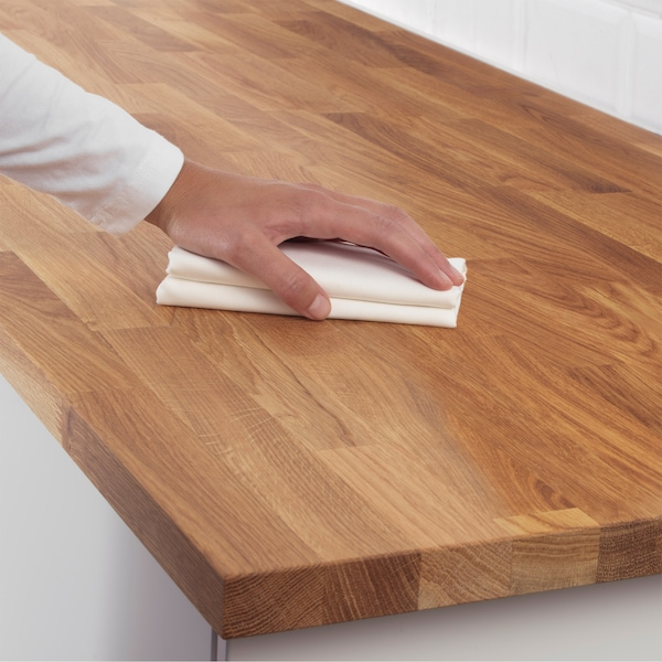 A hand holds a white cleaning cloth against the surface of a wooden kitchen worktop.