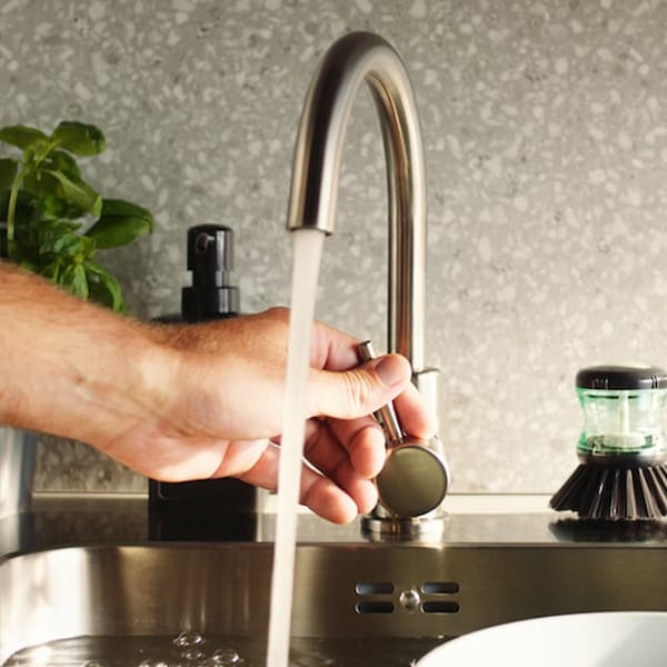 A hand is reaching out to turn off a silver sink faucet.