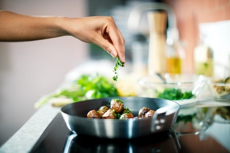 A hand is shown adding herbs to a frying pan of plant balls