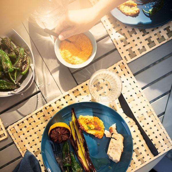 A hand picking up a spoon from a bowl of dip on a wooden table, surrounded by blue plates holding barbecued vegetables.