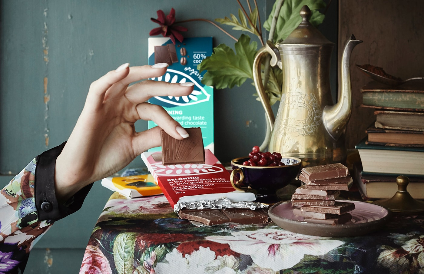 A hand picking up a square of chocolate and a table decorated with chocolate bars, books and fruits.