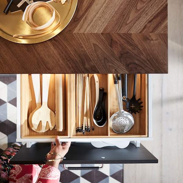 A hand pulling out a drawer below a dark wood countertop with a wooden insert that's filled with kitchen utensils.