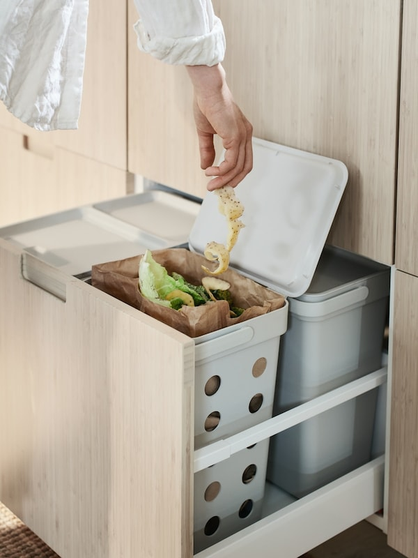 A hand that puts potato peel into a bin for organic waste, one of four HÅLLBAR waste bins with lids inside a kitchen drawer.