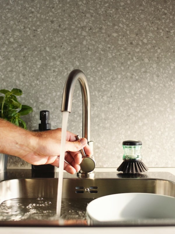 A hand turning off a kitchen faucet which is filling a sink with dishes.