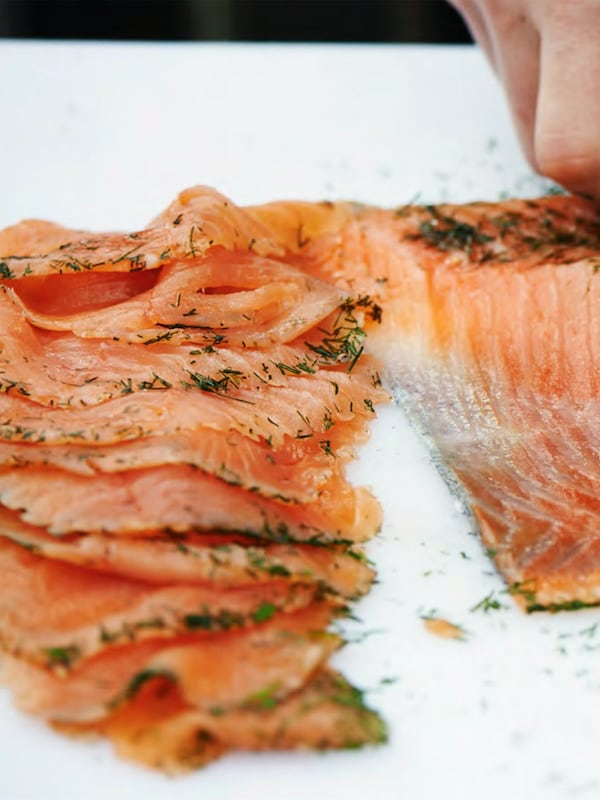 A handful of SJÖRAPPORT is seen on the left, and a hand with the whole piece of cured salmon is on the left, on a white surface.