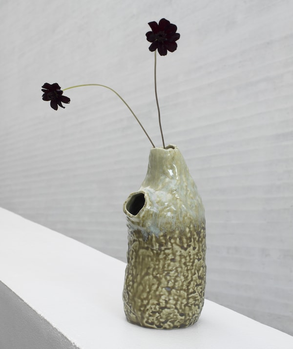 A handmade, irregular ceramic vase from the IKEA ANNANSTANS collection with black flowers in one of two small openings.