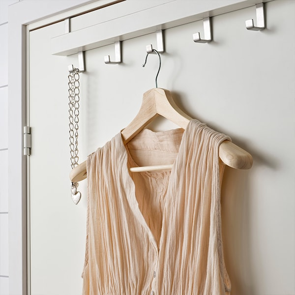 A hanger with a sleeveless top hanging from a rail with hooks.