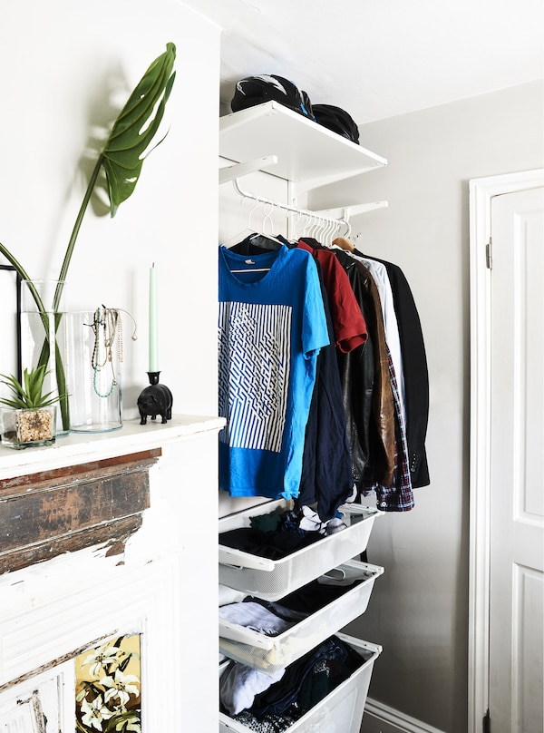 A hanging rail and drawers in an alcove.