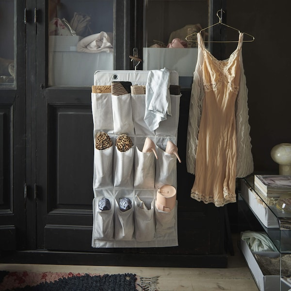 A hanging white shoe organizer hanging from the knob of a dark closet cabinet.