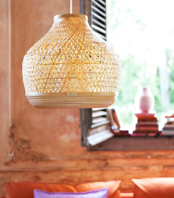 A hanging, woven pendant lamp in front of an orange wall, with dark wooden shutters and books in the background.