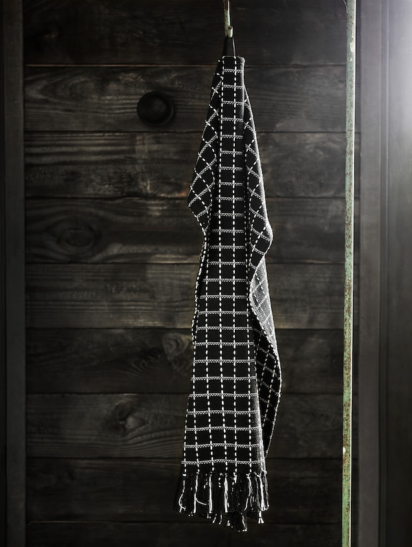A HANTVERK hand towel hanging from a hook. Handwoven by skilled artisans in India.