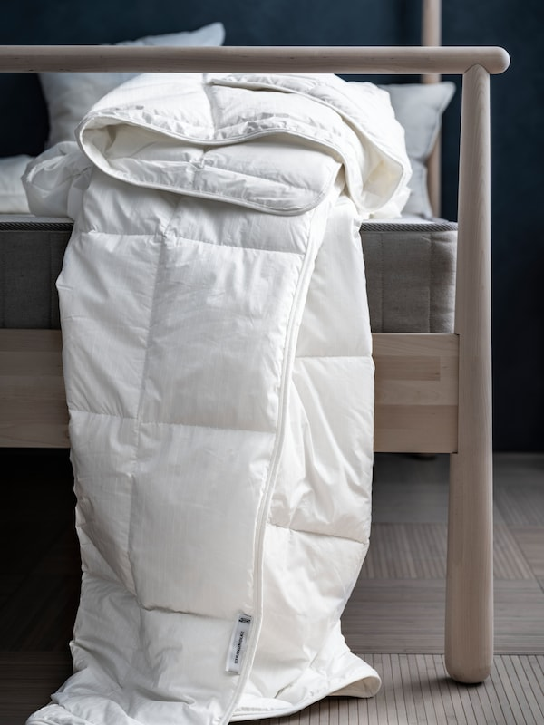 A haphazardly folded, quilt-cover-less STRANDMOLKE duvet spilling over the side of a GJÖRA birch bed in a dimly lit bedroom.