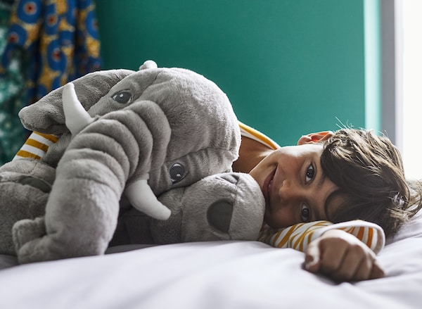 A happy boy lying on a bed in a dark green bedroom with a gray JÄTTESTOR elephant soft toy.