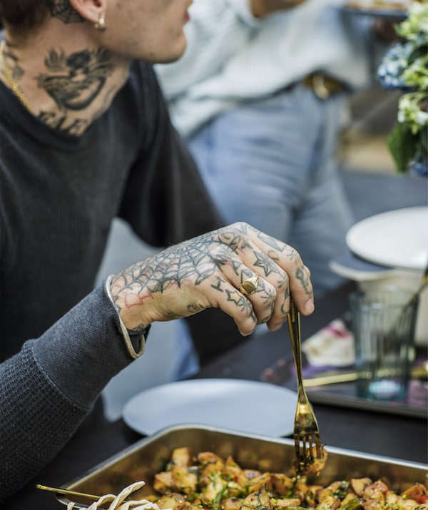 A heavily tattooed man holding a fork above a tray of food.