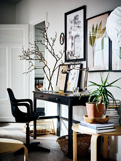 A HEMNES desk with a vase of branches on top, against a white wall covered with pictures. A swivel chair is in front.