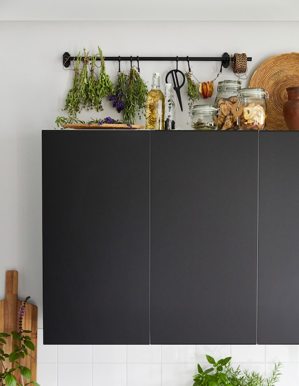A herb drying rack created from a black FINTORP rail above black kitchen wall units.