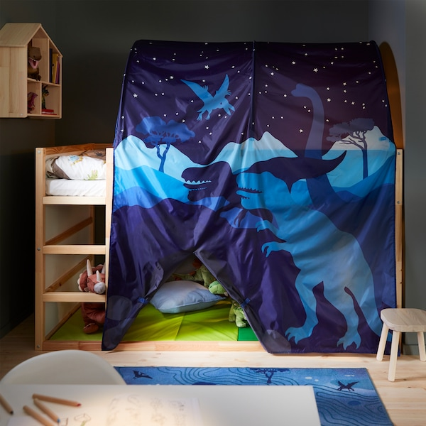 A high bed in white/pine, a blue bed tent with dinosaur pattern, a green folding gym mat, a blue rug and a white desk.