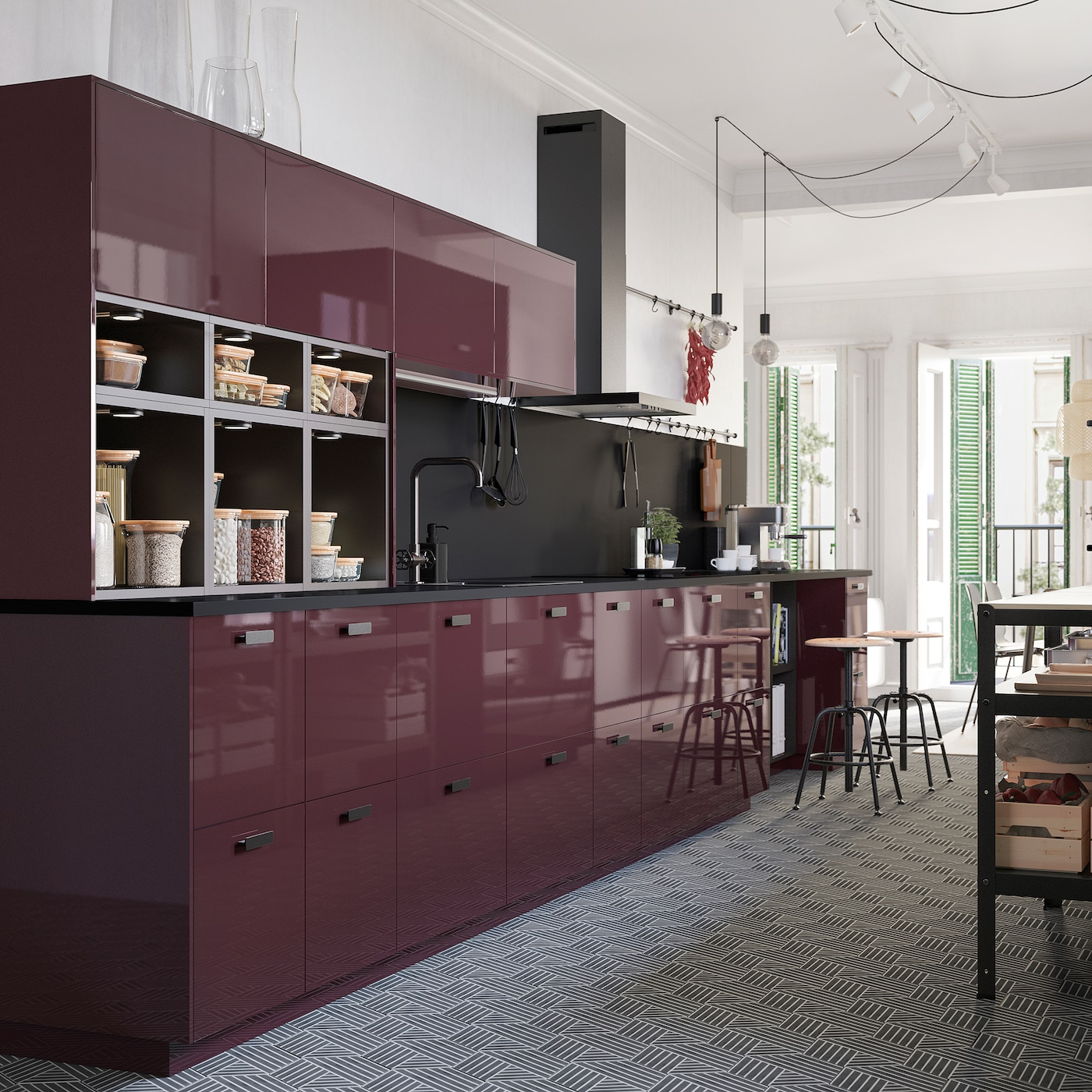 A high-gloss kitchen in dark red-brown, a hexagon-patterned floor and naked light bulbs on cords that hang from the ceiling.