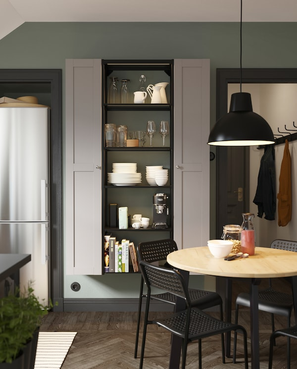A high shelving unit in anthracite, two high cabinets in grey, a round wooden table, black chairs and a black pendant lamp.