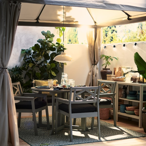 A HIMMELSÖ gazebo on a sunny and leafy garden terrace with a grey BONDHOLMEN table and chairs under it set for a cosy meal.