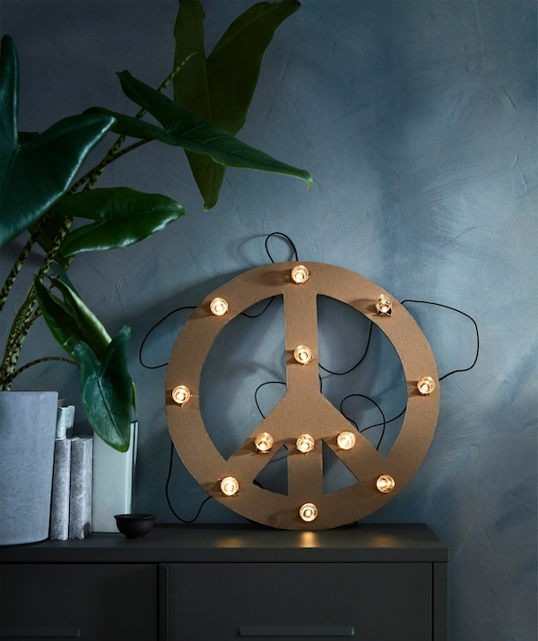 A home-made cardboard peace symbol decorated with an IKEA BLÖTSNÖ LED lighting chain.