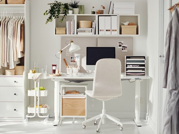 A home office setup in a living room, with a table and white office chair
