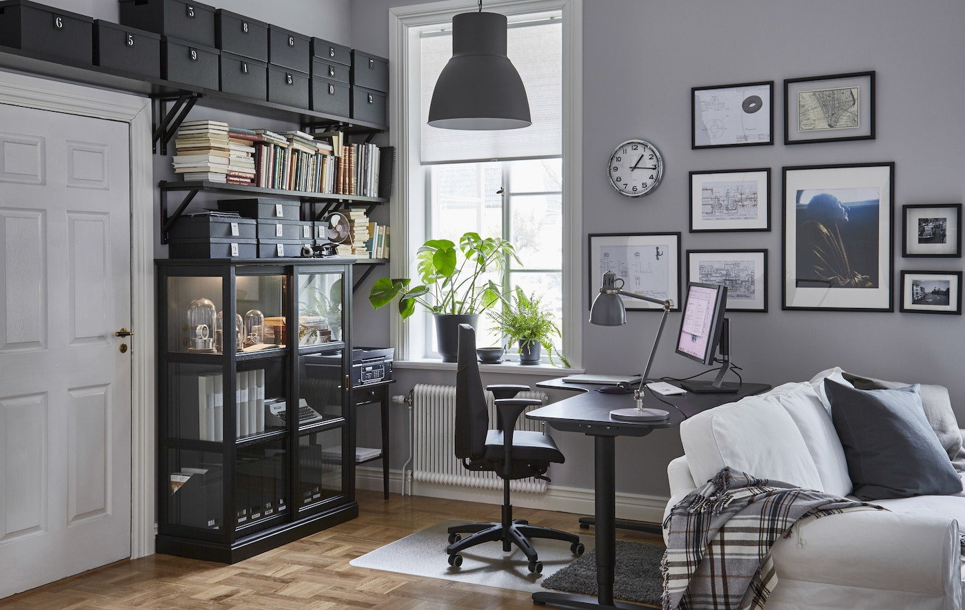 A home office that's ergonomically designed. Includes an adjustable desk, office chair, storage shelves, and plants.