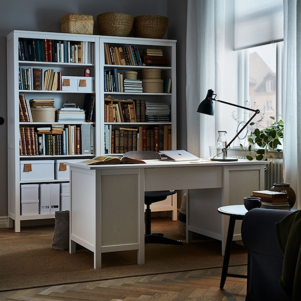 A home office with a white desk and filled bookshelves.