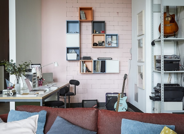 A home office with pink wall.