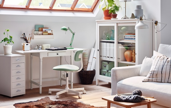 A home office with white desk, chair and storage unit.
