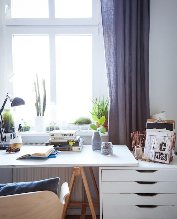 A home office work station, including desk and cabinet, placed in front of a large window.