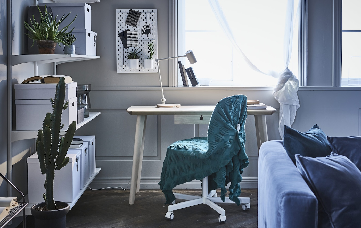 A home office workspace in a living room. Includes a desk, a chair draped in a throw, and open storage shelves