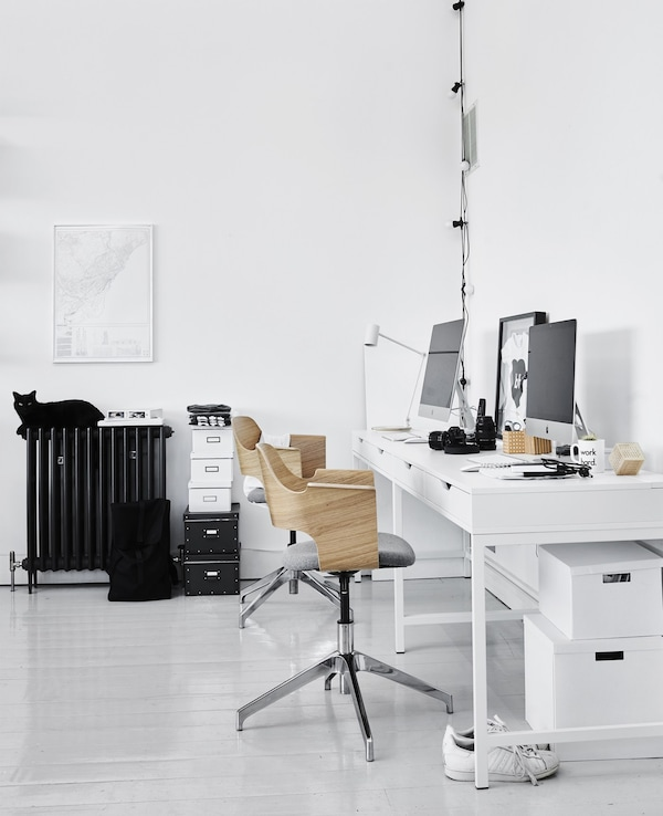 A home office workspace in the living room including two modern swivel chairs with wood backing and white work desks.