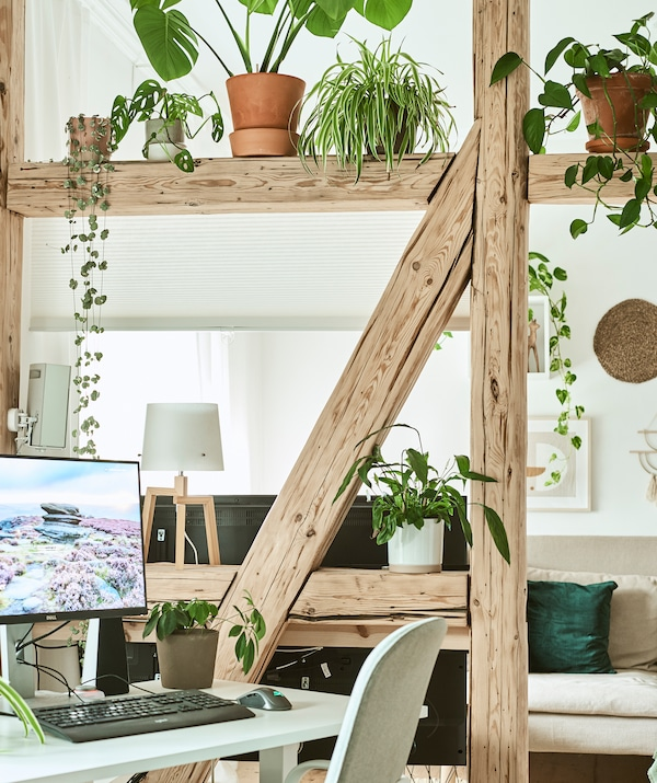 A home office zoned off from the main living room by A-frame timber beams, plants and a blind that lowers to create a screen.